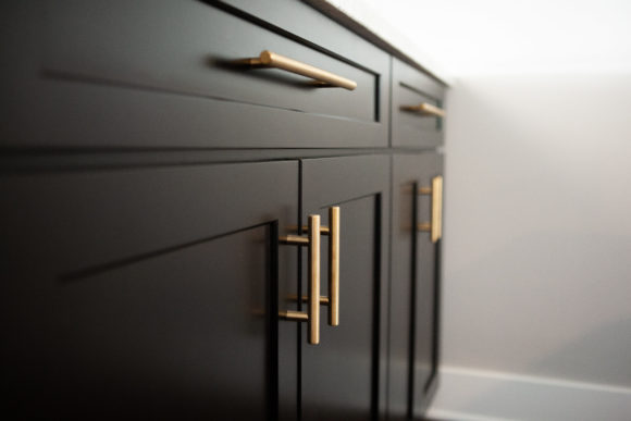 Basement Finish in Andover: Dark cabinets with gold handles